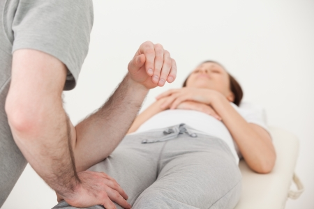 Masseur massaging the thigh of a woman in a physio room Stock Photo - 16204917