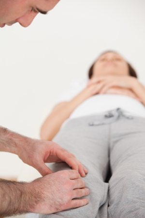 Woman lying on her back while a physiotherapist  massing her knee in a room Stock Photo - 16204770