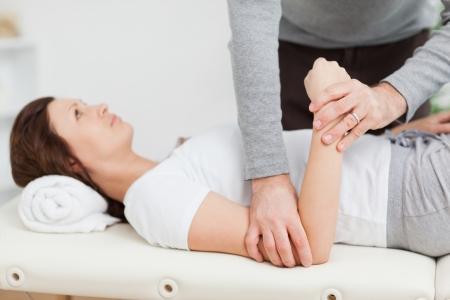 elleboog: Fysiotherapeut manipuleren van de arm van een vreedzame vrouw in een kamer