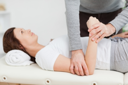 muscle retraining: Physiotherapist manipulating the arm of a peaceful woman in a room