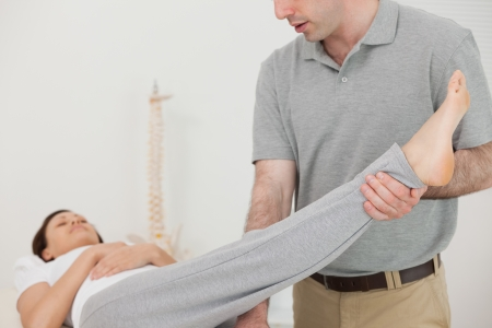 muscle retraining: Brunette woman lying while a therapist is stretching her leg indoors Stock Photo