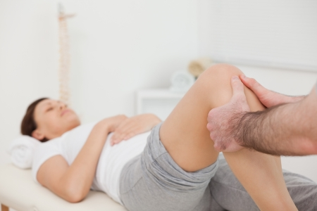 Woman lying while being massaged by her practitioner indoors photo