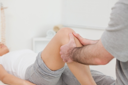 lower limb: Man massaging the leg of a woman in a room Stock Photo