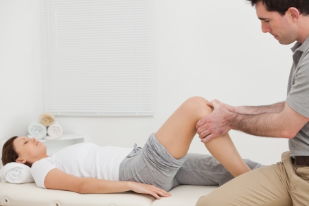 Man massaging the knee of a woman while sitting in a room photo