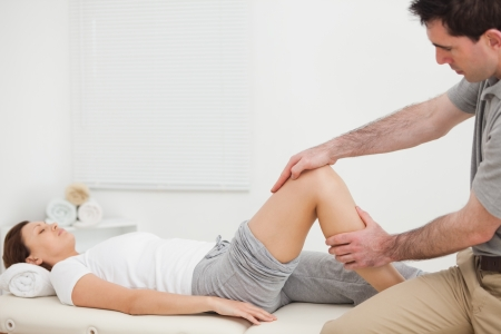 lower limb: Woman lying while a man manipulating her leg indoors