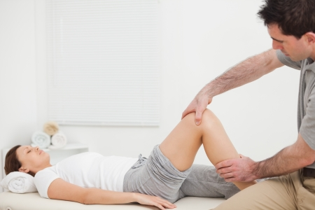 Brunette woman lying while a physiotherapist manipulates her leg indoors Stock Photo - 16203784