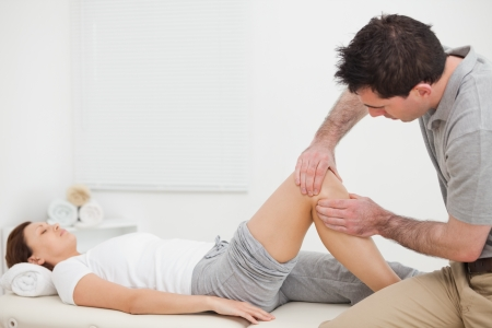 lower limb: Brown-haired man massaging the knee of a woman in a room