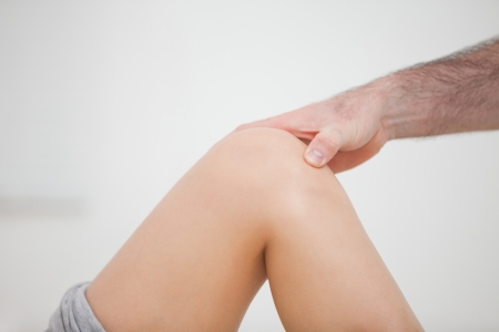 lower limb: Close-up of a physiotherapist touching a knee in a room Stock Photo