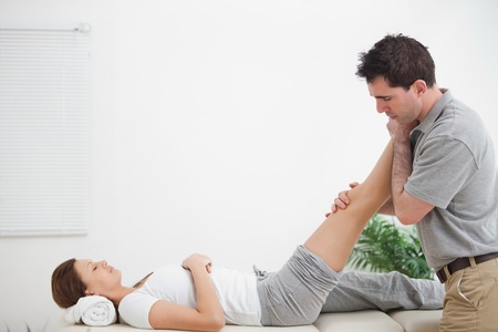 Chiropractor massaging a leg while placing it on his shoulder  in a room