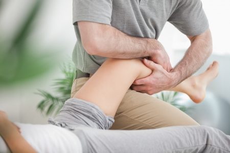 joint mobilization: Man manipulating the leg of a woman while she is lying in a room Stock Photo