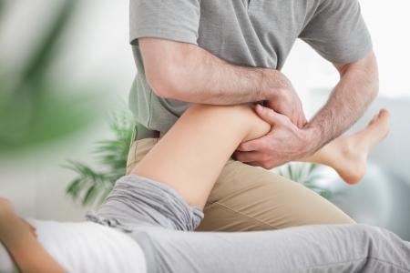 fysiotherapie: Man manipuleren het been van een vrouw terwijl ze ligt in een ruimte