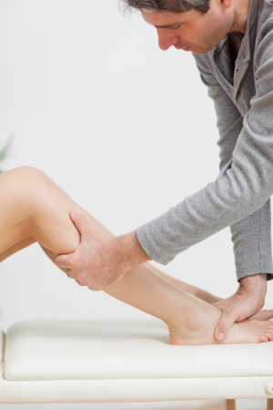 neuromuscular reeducation: Serious osteopath holding the calf of a patient in a medical room