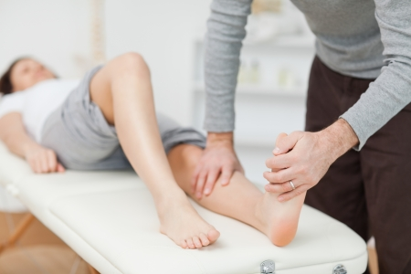 foot doctor: Physiotherapist stretching a barefoot in a room