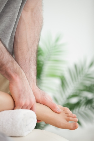 muscle retraining: Close up of hands massaging a foot in a room