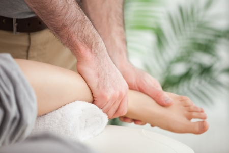 muscle retraining: Close-up of a foot being massaged by a doctor in a room Stock Photo