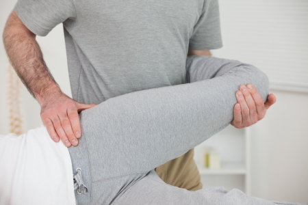 muscle retraining: Chiropractor stretching the leg of a patient in a room
