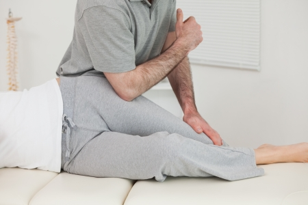 muscle retraining: Patient lying on the side while being massaged in a room