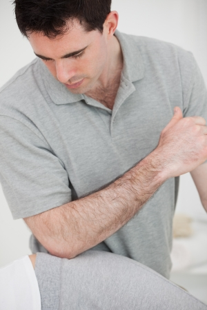 Physiotherapist using his elbow on the hip of a woman in a room Stock Photo - 16208280