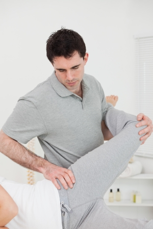 muscle retraining: Physiotherapist standing behind a woman while stretching her leg in a room Stock Photo