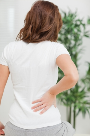 back sprains: Brunette sitting while massaging her painful back in a room