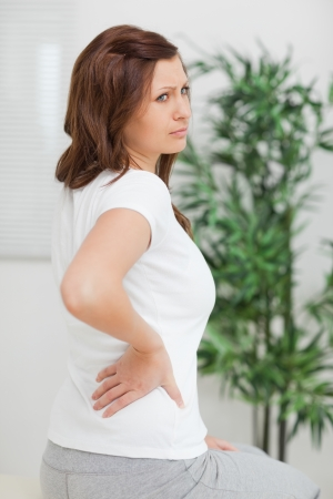 spinal conditions: Woman touching her back while looking away in a room