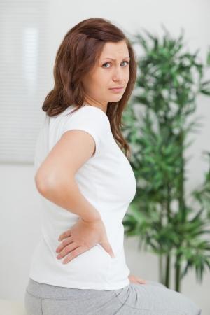 mujeres de espalda: Brown-haired mujer tocando su espalda dolorosa en una habitaci�n