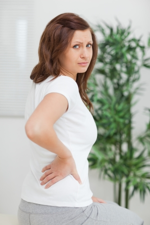 spinal conditions: Brown-haired woman touching her painful back in a room Stock Photo