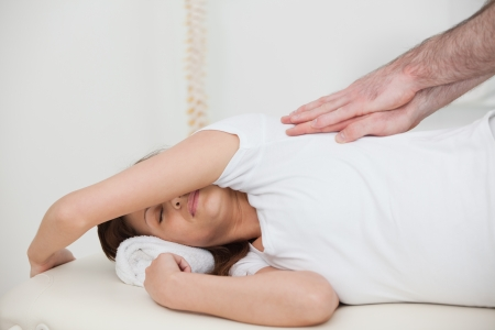 Woman lying on the side while being massaged in a room photo
