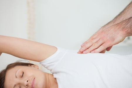spinal conditions: Peaceful patient being massaged by a doctor in a room Stock Photo