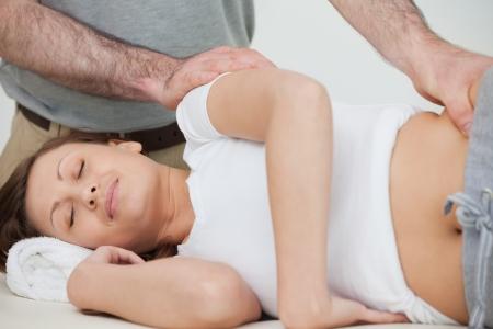 osteopata: Mujer morena que recibir� el masaje por su oste�pata en una habitaci�n Foto de archivo