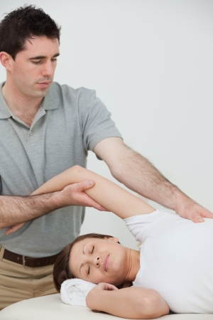 spinal conditions: relaxed woman being stretched by a physiotherapist in a room