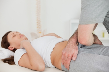 osteopath: Brunette woman lying while a physiotherapist touching her hips in a room