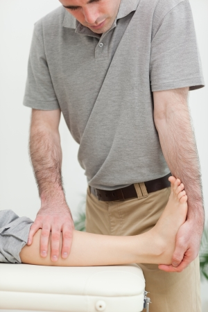 Serious physiotherapist stretching the leg of a patient in a room photo