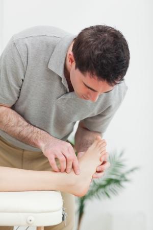 tendones: Podiatrist examinar el pie de un paciente en una habitaci�n