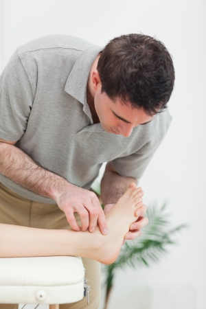 podiatrist: Podiatrist examining the foot of a patient in a room