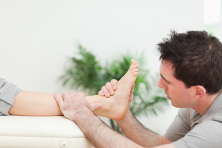 Physiotherapist sitting while massaging a foot in a room Stock Photo - 16203320
