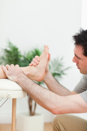 Close up of a physiotherapist massaging a foot in a room Stock Photo - 16202927