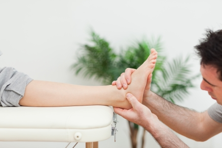 muscle retraining: Close-up of a doctor massaging a foot in a room Stock Photo