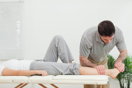 Chiropractor examining the foot of a woman in a room