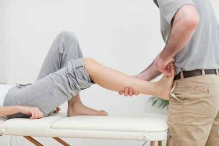 ligaments: Close-up of a physiotherapist stretching the foot of a patient in a room