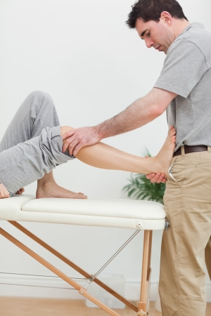 naprapathy: Brunette physiotherapist stretching a foot in a room