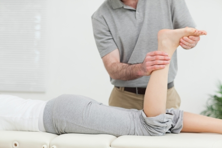 neuromuscular reeducation: Woman lying forward while a physiotherapist examining her leg in a room Stock Photo