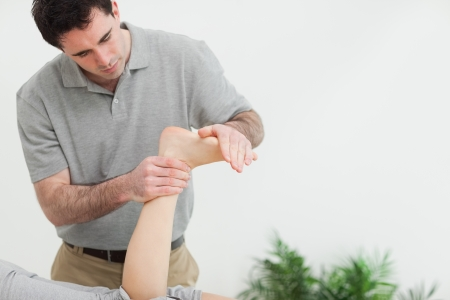 Brown-haired therapist stretching the foot of a patient in a room Stock Photo