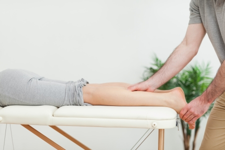 Woman lying while a masseur massaging the calves in a room Stock Photo - 16203893
