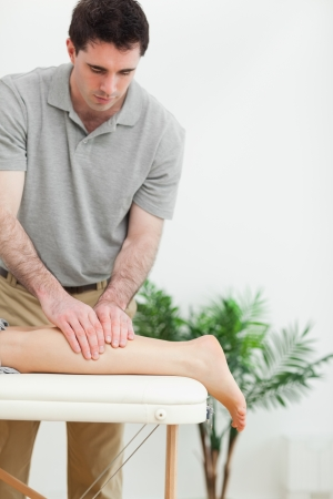 neuromuscular reeducation: Brunette masseur massaging the leg of a woman in a room Stock Photo