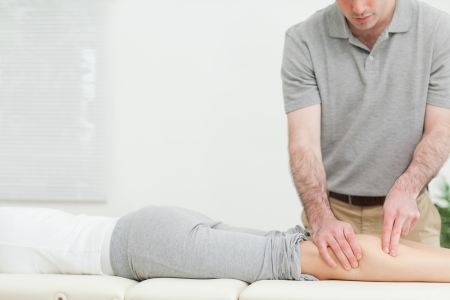 Woman lying forward while a physiotherapist massaging her leg in a room photo