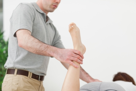 neuromuscular reeducation: Woman lying while being stretched by a man in a room