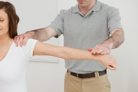 Woman sitting while a doctor is examining her arm in a room