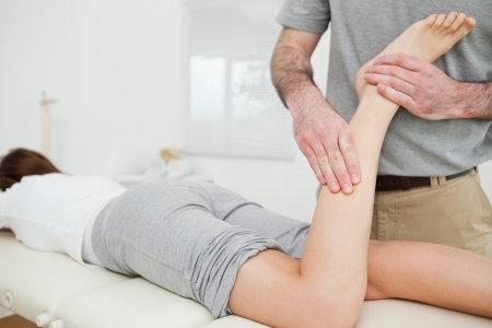 Woman lying while a doctor is examining her leg in a room Stock Photo - 16204456