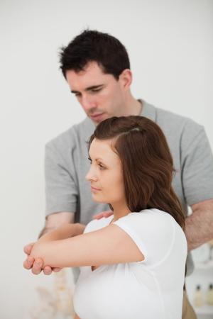 douleur epaule: Grave docteur étirer le bras d'un patient dans une chambre